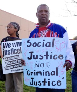 Martel Miller (foreground) and Sophia Lewis stand outside the satellite jail demanding justice