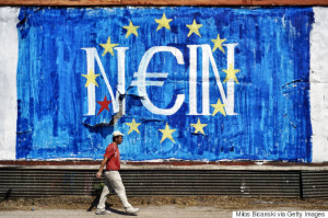 ATHENS, GREECE - JUNE 30: A man walks past anti-EU graffiti on June 30, 2015 in Athens, Greece. Greek voters will decide in a referendum next Sunday on whether their government should accept an economic reform package put forth by Greece's creditors. Greece has imposed capital controls with the banks being closed until the referendum and a daily limit of 60 euros has been placed on cash withdrawals from ATMs. (Photo by Milos Bicanski/Getty Images)