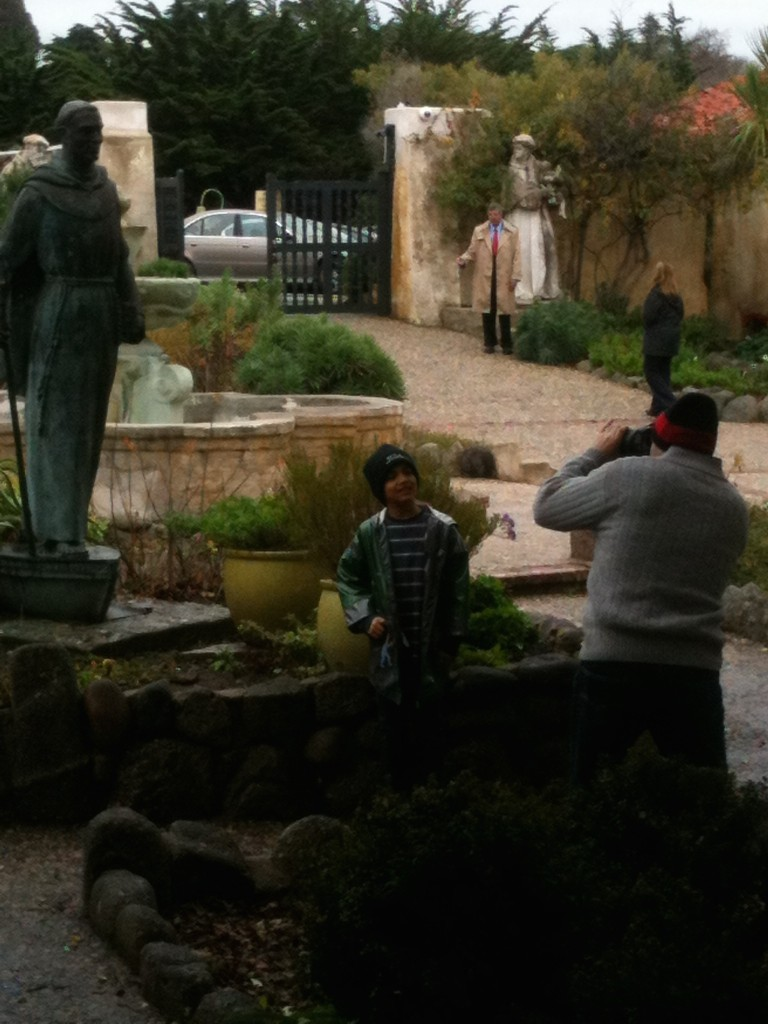 Visitors at the Carmel Mission statue that had been vandalized.